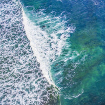 Looking down at surfers in white ocean waves - aerial view
