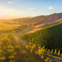 Aerial panorama of sunset over countryside - winding road, forested hills and golden colors