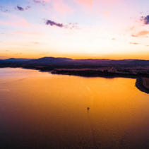 Lone boat sailing across scenic lake at vivid orange sunset - aerial view