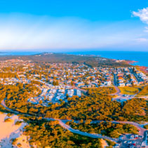 Beautiful aerial panorama of Anna Bay township and ocean coastline at sunset. Anna Bay, New South Wales, Australia