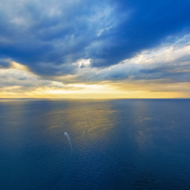 Aerial view of lonely boat sailing across ocean at beautiful sunset