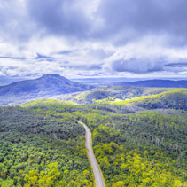 Aerial view of rural highway among mountains and forest in Tasmania, Australia