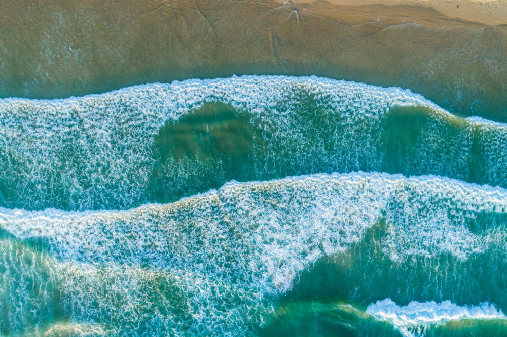 Looking down at ocean waves pound on the shore