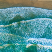 Looking down at ocean waves pound on the shore - aerial view