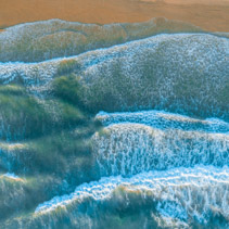 Ocean waves pound on the shore - aerial view