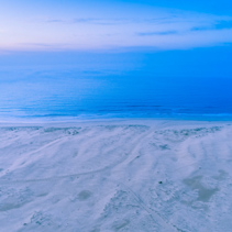 Aerial view of ocean coastline at dawn. Nothing but White sand, blue water and sky.