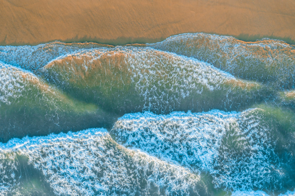 Ocean waves roll and crash into the shore at sunrise