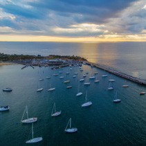 Aerial view of moored boats and long pier at sunset. Mornington