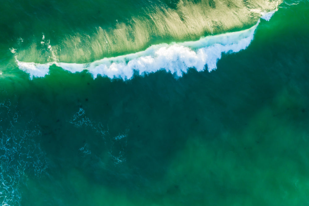 Crushing green ocean wave at sunset. Aerial view with copy space.