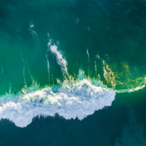 Looking down at crushing ocean wave at sunrise. Aerial view with copy space.