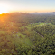 Sunset with sun flare over beautiful rural area - aerial panorama