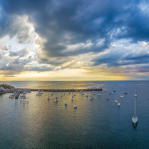 Aerial Panorama of Mornington Pier and moored yachts at beautiful vivid sunset and cloudscape. Melbourne, Victoria, Australia