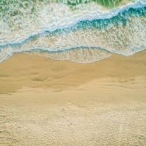 Aerial landscape of powerful ocean waves rolling into the sandy beach