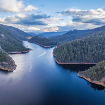 Beautiful Cethana lake and surrounding forest aerial panorama