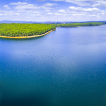 Aerial panorama of beautiful blue lake and forest under white fluffy clouds in Australia
