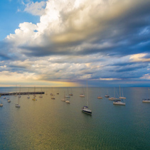 Aerial view of moored boats and long pier at sunset