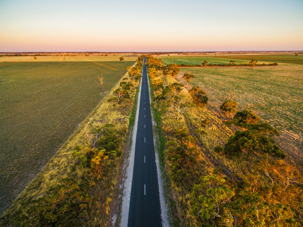 Long straight road in rural area among green fields and pastures