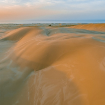 Sand dunes near the ocean at sunset