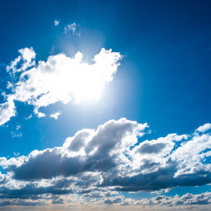 Blue sky with sun shining through white clouds background overlay