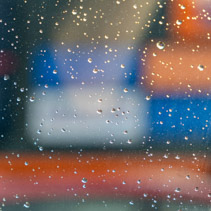 Splashes of blurred color behind window with water droplets - abstract background overlay