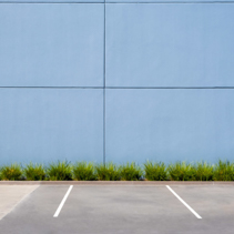 Empty parking spaces against clean concrete wall of an industrial building with pach of grass