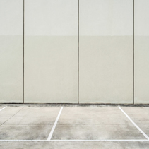 Empty parking lot next to concrete wall - clean geometric architecture shapes