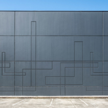 Dark gray concrete wall of industrial building with geometric pattern