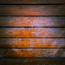 Wooden planks with peeling orange paint background texture