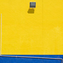 Large wall of building exterior painted in yellow and blue with pipe, flood light and copy space