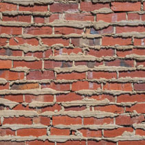 Retro red brick wall with cement filling oozing out