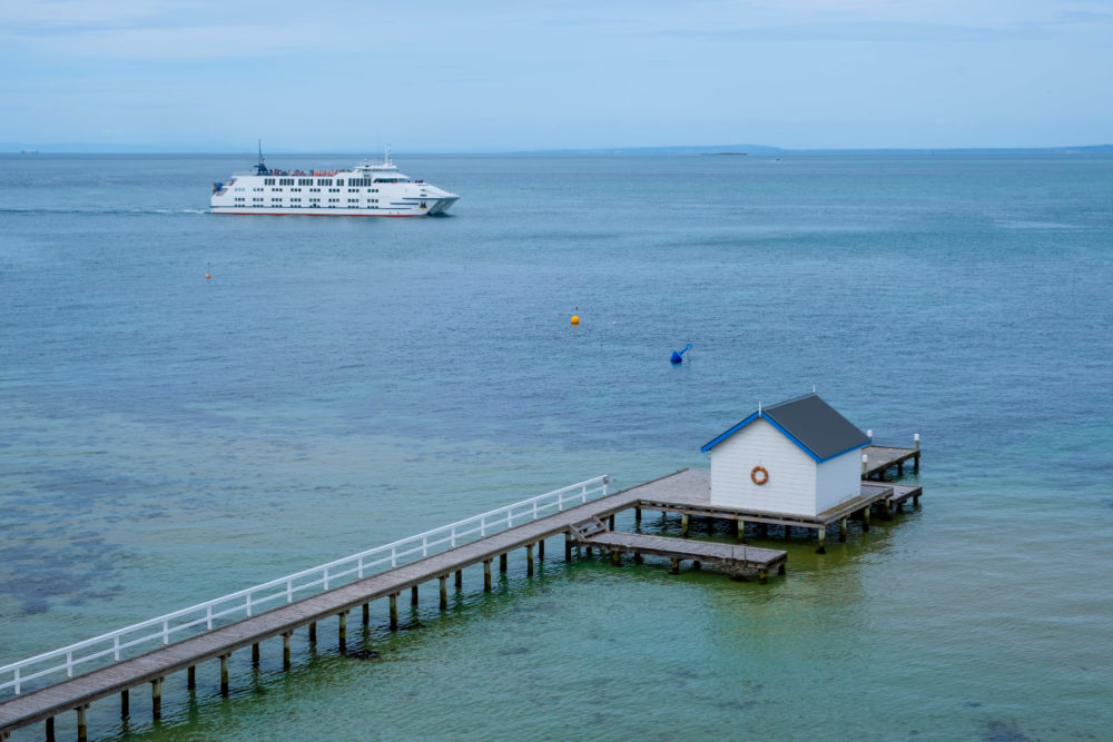 Passenger ferry crossing Port Phillip Bay behind wooden pier