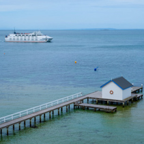 Passenger ferry crossing Port Phillip Bay behind wooden pier