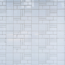 White tiles wall arranged in geometric pattern background