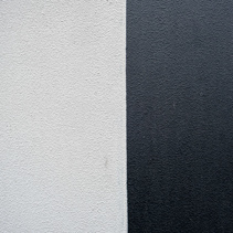 Textured concrete wall divided in two sections - black and white