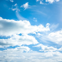 Bright blue sky with white fluffy clouds and shining sun background texture