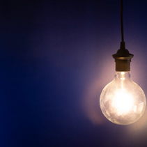 Big glowing light bulb against blue wall with copy space