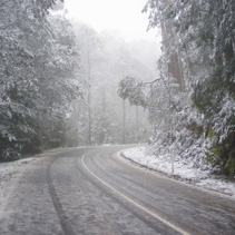 Slippery and icy winding mountain road under heavy snowfall