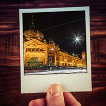 Hand holding instant photo postcard of Flinders Street Station