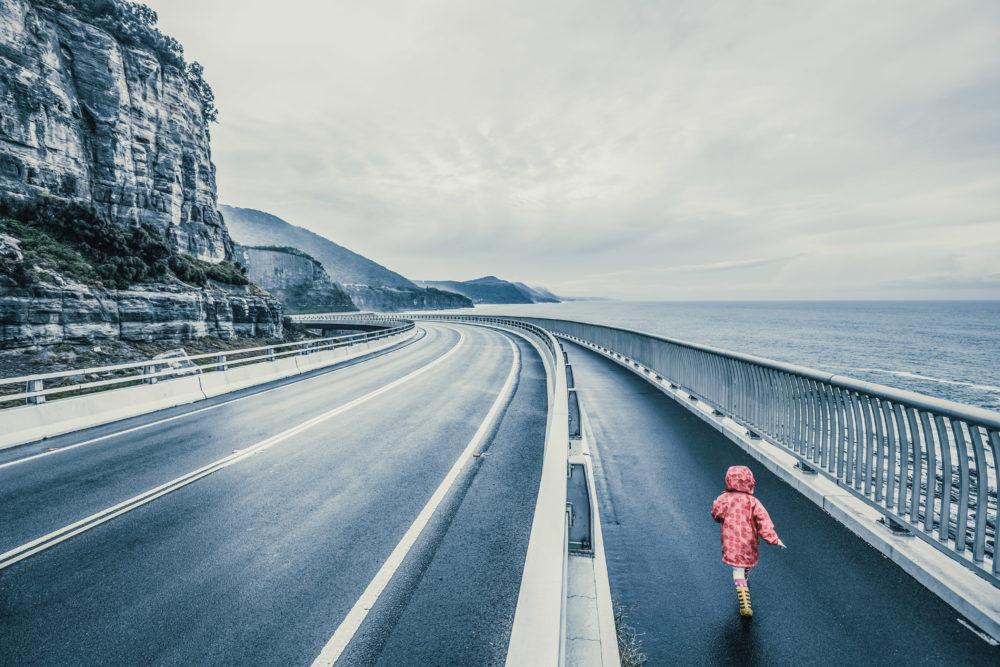 Child running on Sea Cliff Bridge, Grand Pacific Drive, Sydney, Australia. Image has vintage filter applied.