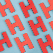 Seamless pattern of red capital letters H on blue background