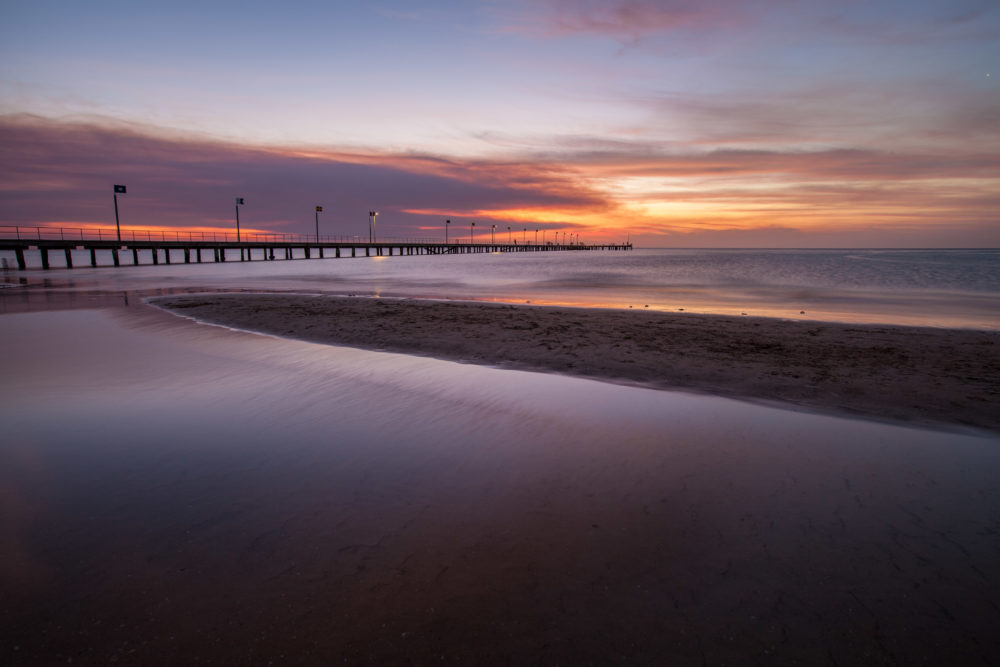 Smooth water surface and pier in orange sunset colors