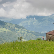 Lonely boy standing near his hut, amongst rice fields, in Kathmandu Valley, Nepal