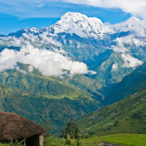 View of snowed mountain peak above the green valley in Himalayas, Nepal