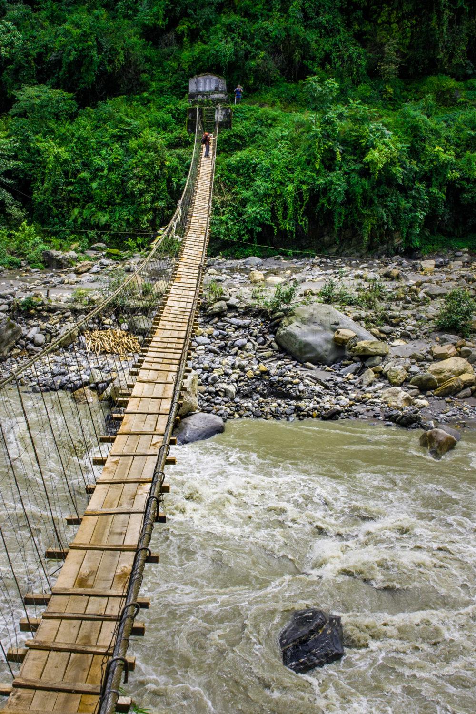 Narrow hanging bridge over mountain river in Himalayas, Nepal.