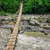 Narrow hanging bridge over mountain river in Himalayas, Nepal.
