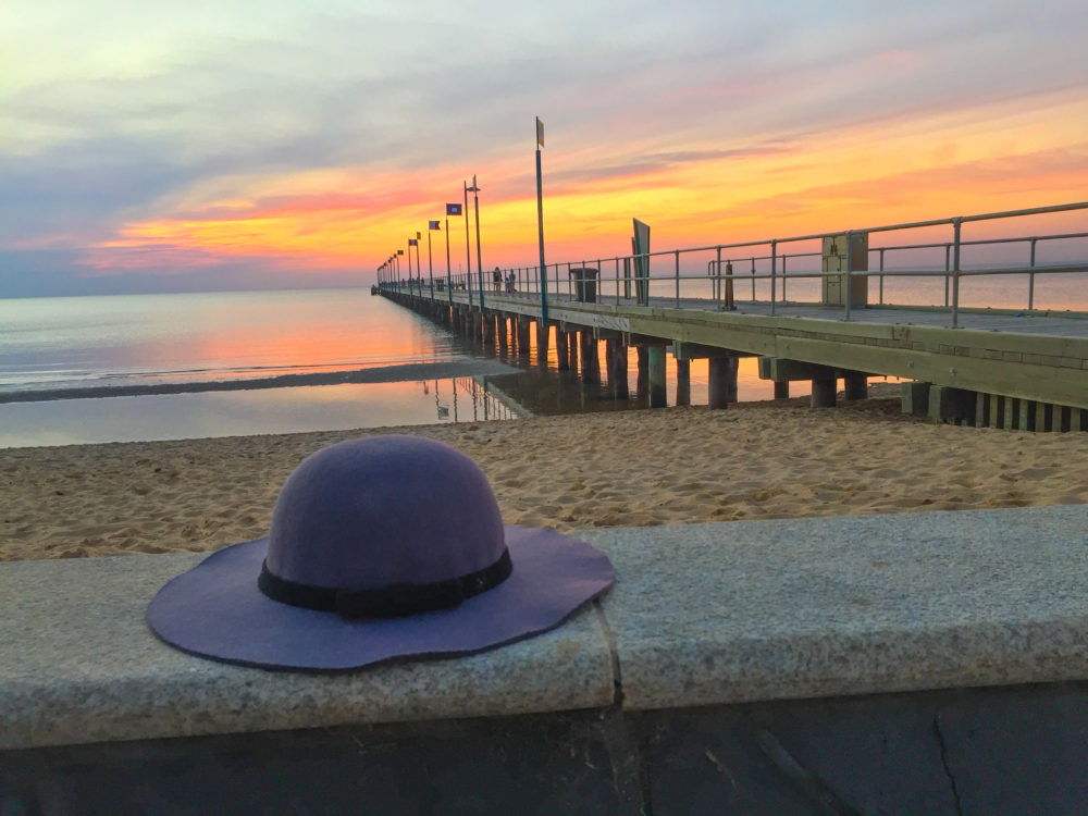 Woman's hat forgotten on a ledge near wooden pier at sunset