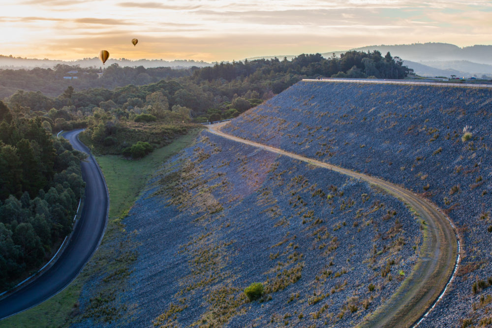 Hot air balloons at sunset above forest