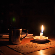 Tin mug and glowing candle on wooden table in the dark.