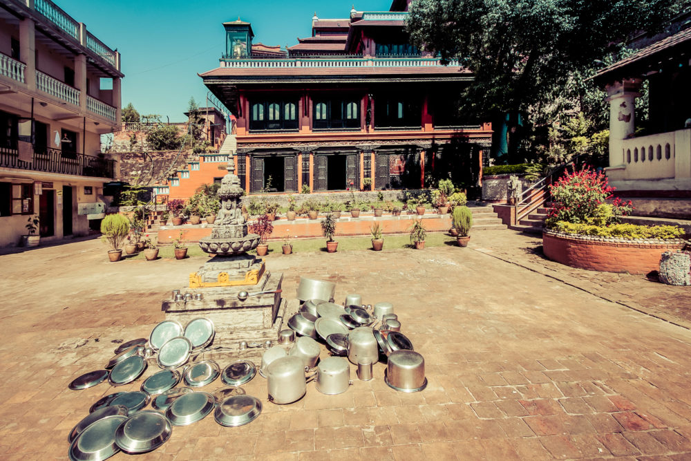 Metal dishes left to dry out in the sun in front of a Buddhist monastery
