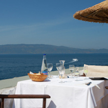Table with glassware at outdoor restaurant, Hydra Island, Greece.